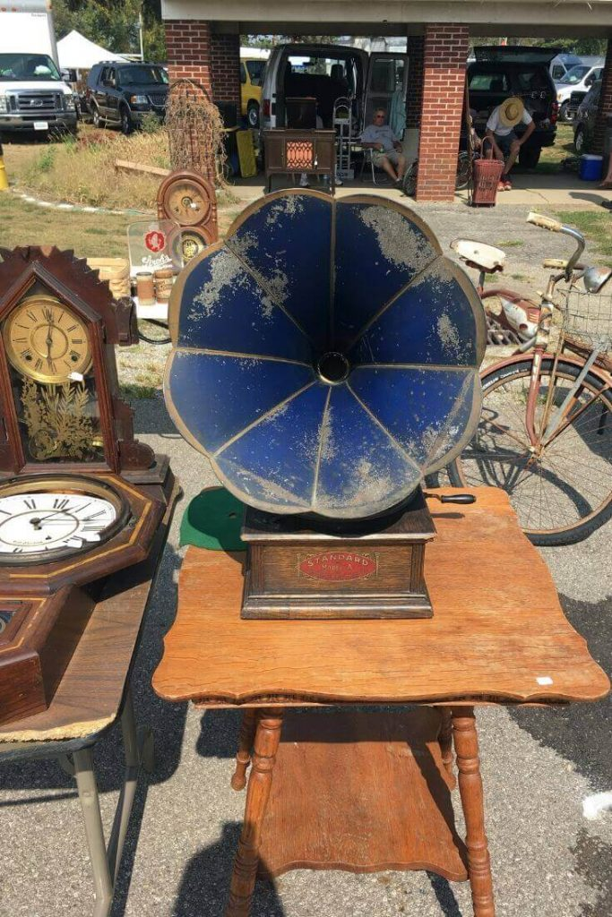 Blue phonograph sitting on top of an antique table at the flea market.