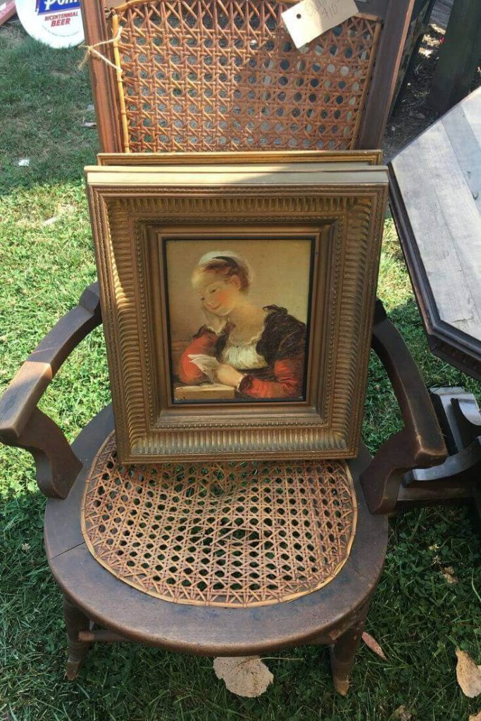Vintage cane chair with small framed portrait of a woman resting on seat.