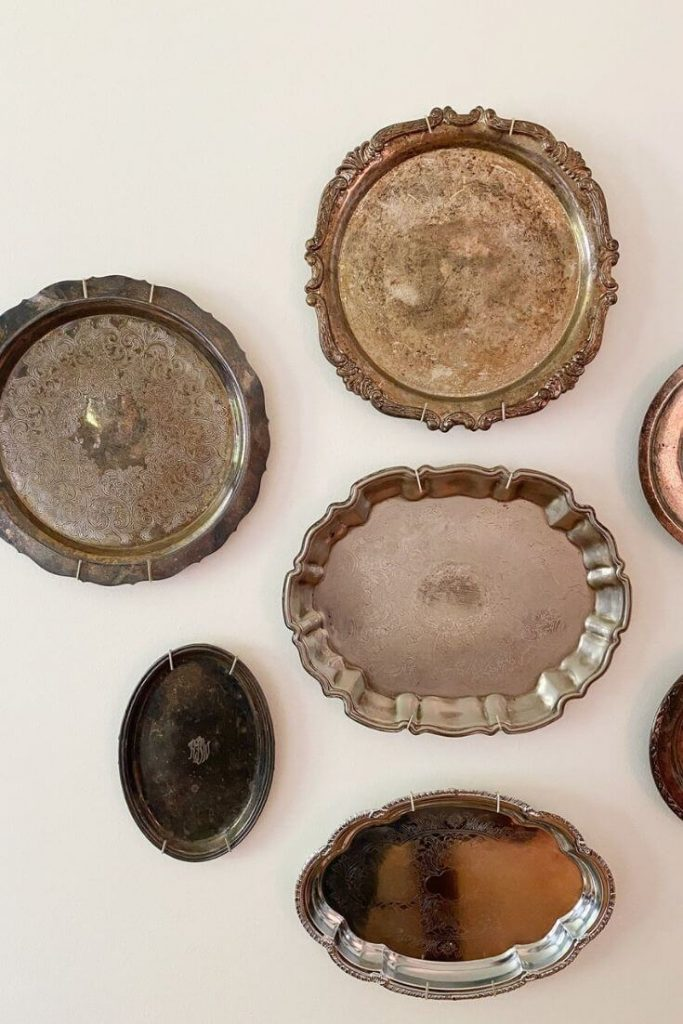 An arrangement of antique silver platers hang on the white wall of our dining room to add some character to the space.