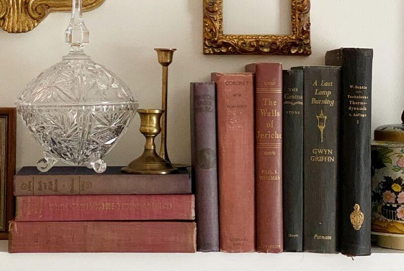 A new glass candy dish displayed with an assortment of antique books and brass candle sticks adds character to our guest bedroom mantel