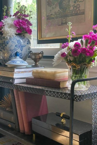 Metal console table displaying fresh flowers, books, and other accessories in front of a window
