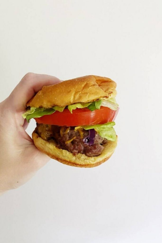 A hand holding a burger with lettuce, tomato, and cheddar cheese in front of a white wall