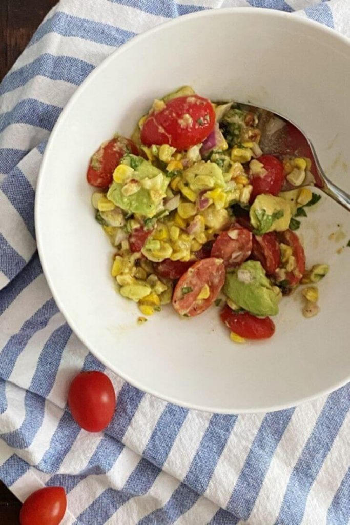 Looking down on a white bowl with corn, avocado, and tomato salad on top of a blue and white striped towel with 2 cherry tomatoes off to the side on the towel.