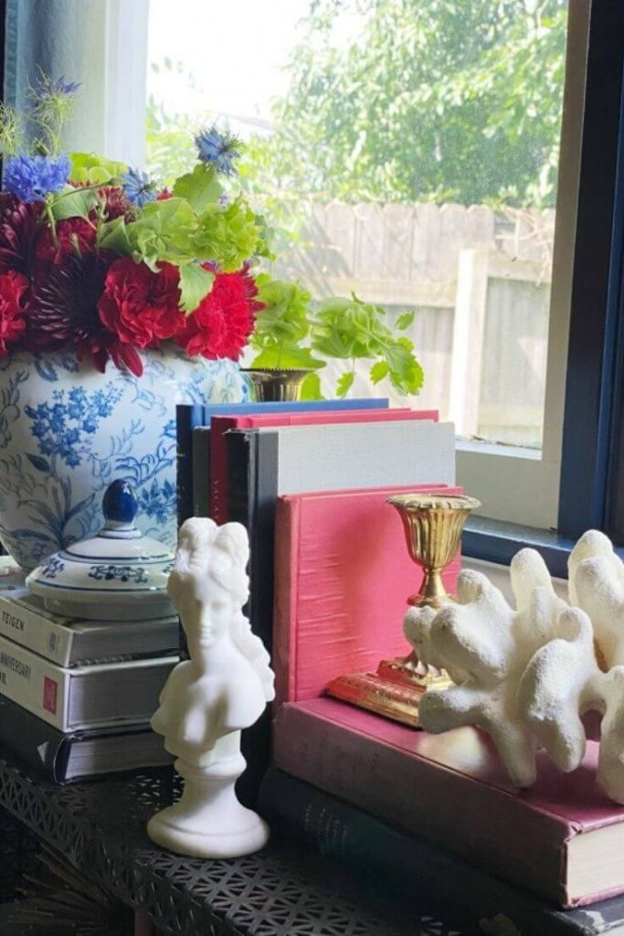 Vignette of books, blue and white pottery with fresh red and blue flowers and greenery, small white bust of woman, and white coral