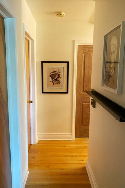 View into our second-floor hallway with white walls, hardwood floors, 3 door openings and two pieces of artwork on the walls