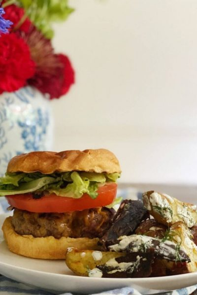 Burger loaded with lettuce, tomato, and cheddar, side of roasted potatoes with sour cream dressing, on a white plate next to a a vase of flowers