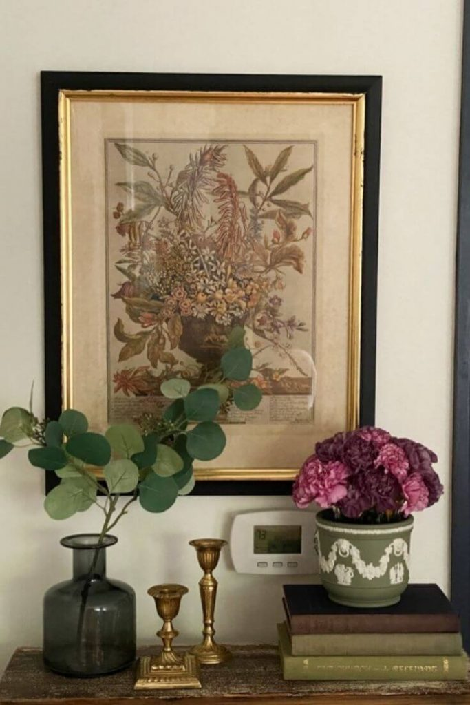 Vignette with framed floral hanging on wall, bouquet of fresh flowers in jasper ware vase atop a stack of books, gold candle sticks, and greenery in glass vase