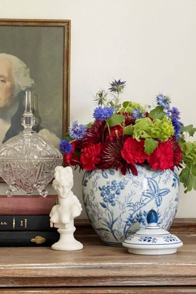 Portrait of George Washington hanging on wall behind console with a glass candy dish atop a stack of books, small white bust of woman, and blue and white pottery with fresh red and blue flowers with greenery.