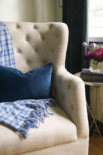 Metal side table with a stack of books and flowers next to a winged beige upholstered with plaid gray and blue blanket and navy velvet pillow