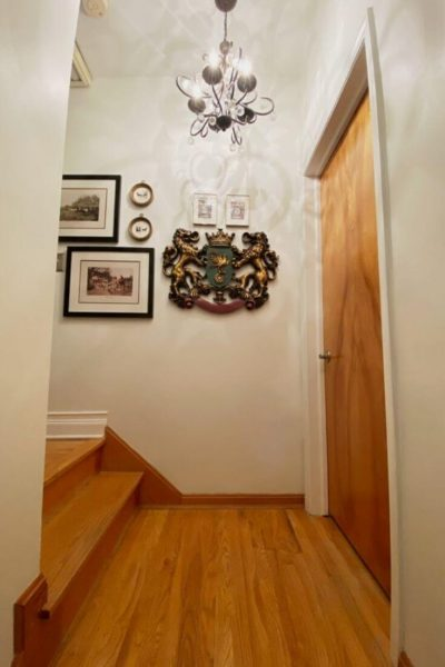 Top of stairs landing. White walls and hardwood floors. Closed door on right and two additional stairs on left. Chandelier hangs from ceiling and a crest and other pieces of art hang on wall