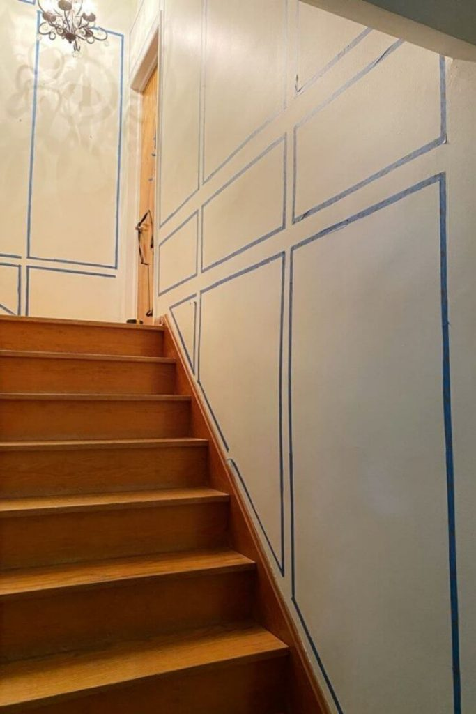 View up the wooden staircase showing the long white wall on the right and at the top of the landing with painters tape mapping a possible layout for picture moulding