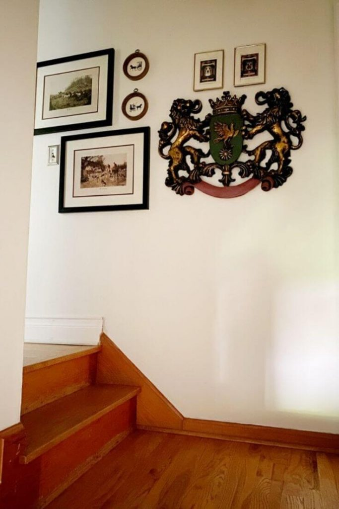 Looking at landing at top of stairs and two additional stairs up to hallway. Hardwood floors and white walls with crest and other pieces of artwork hanging on wall