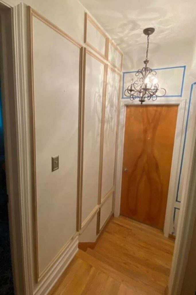 Progress photo of unpainted picture moulding on wall at top of stairs