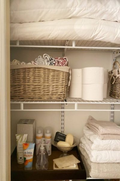 Inside a linen closet with extra pillows on top shelf, Basket for pillowcase and extra toilet paper below and a tray to hold extra toiletries and towels below that