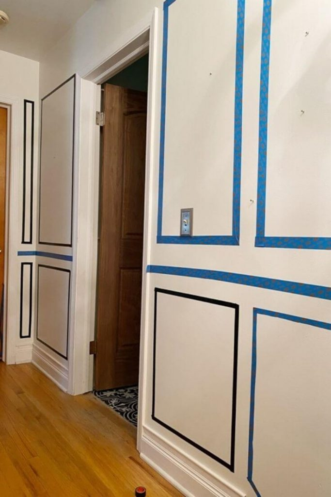 White walls in hallway with painters tape on walls to map out a layout for picture moulding and a chair rail