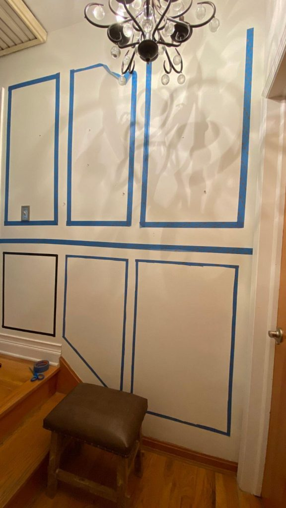 View of white wall at top of staircase with hardwood floors showing a possible layout for picture moulding with chair rail on wall with painters tape