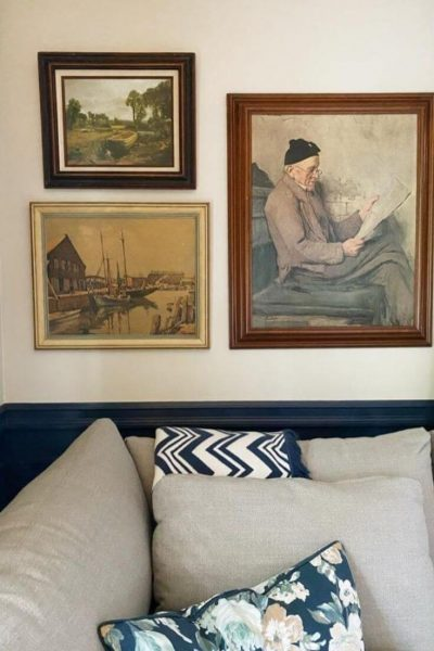Thrifted art hanging on wall above sofa