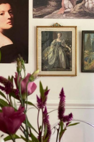 Portraits hanging on wall with flowers in foreground