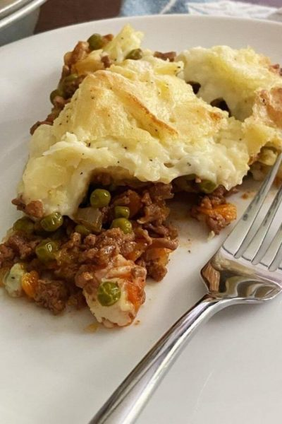 Close up of slice of shepherds pie on a white plate with fork