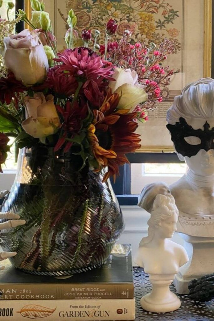 Fall moody floral arrangement on a stack of books with a small bust next to it and a larger bust with a black mask behind