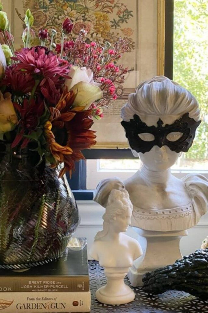 Display for Halloween featuring a moody fall floral arrangement next to a larger bust of woman with black mask and smaller bust of woman in front and gourds