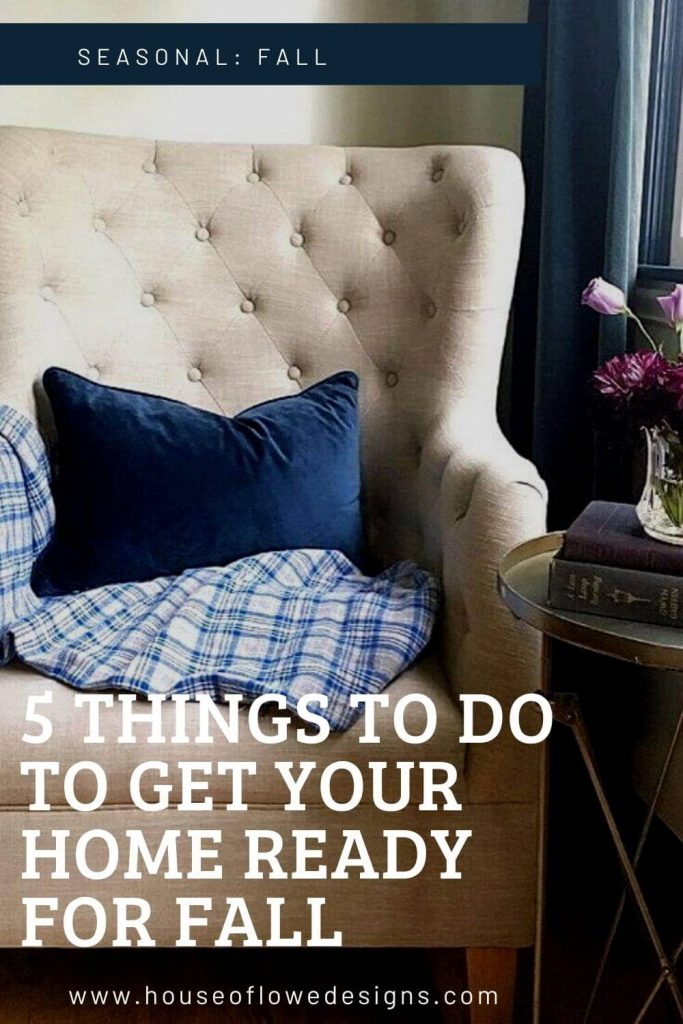 Tufted cream chair with navy pillow and plaid throw next to a metal table with accessories