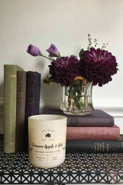 Fall candle on metal console with a stack of books and a small, moody, fall floral arrangement