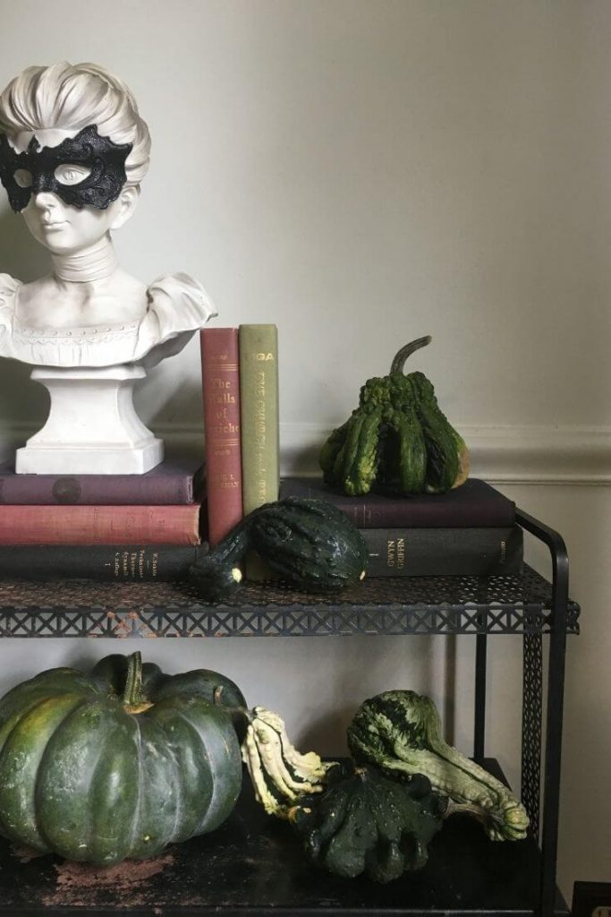 Bust of woman with black mask on top of a stack of books with an assortment of green pumpkins and gourds on a metal console