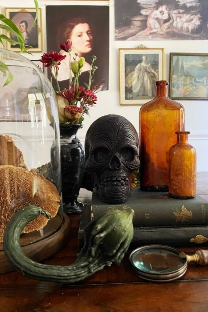 Halloween display of amber bottles and a black skull candle on top of a stack of books with a gourd and magnifying glass in front and florals behind. Cloche with dried mushrooms to the left of display