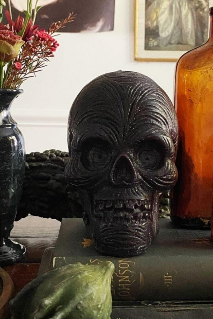 Patch NYC Skull Candle from Crate and Barrel on a stack of books