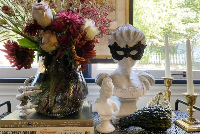 Halloween display in front of a window with moody falll flowers, gourds, brass candle sticks and busts