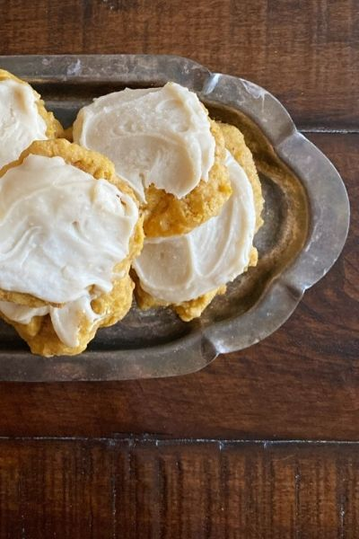 Pumpkin cookies with frosting piled on a silver platter