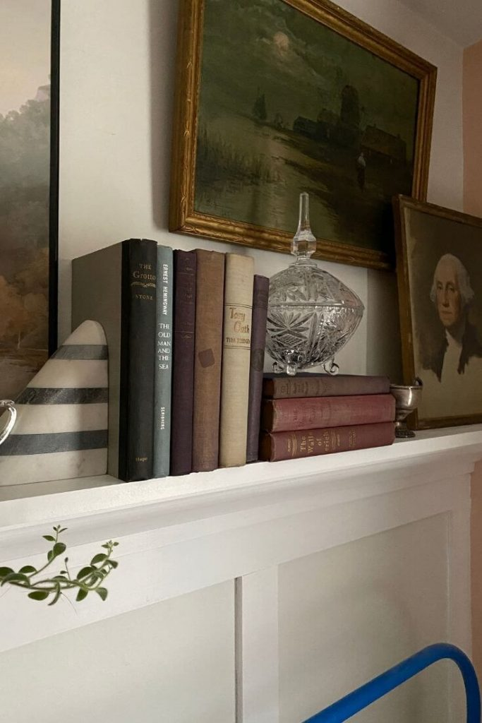 Mantle in guest bedroom styled with art, books, and accessories
