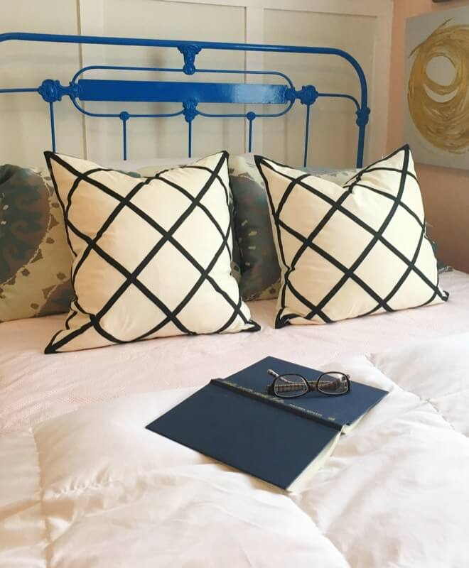 Blue metal bed with throw pillows, duvet and an open book upside down with folded glasses on top