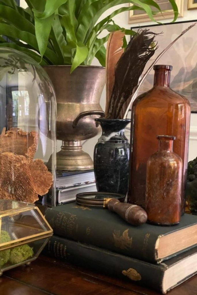 Close up of antique books displaying amber bottles and a magnifying glass
