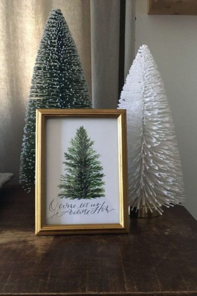 A holiday decor grouping of two bottle brush trees and a framed holiday print