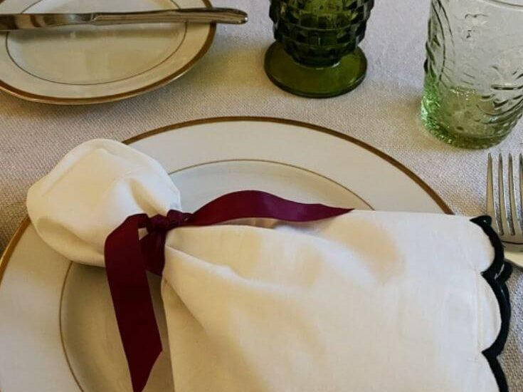 Close up of a table setting with a white cloth napkin tied with a ribbon on a gold rimmed white plate for Thanksgiving Day