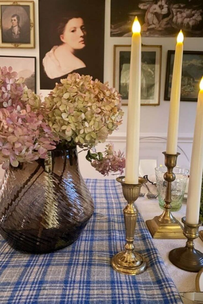 Dried hydrangeas and a grouping of brass candlesticks make for simple and easy Thanksgiving table decor