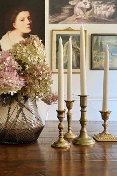 Grouping of brass candle sticks with LED faux candles on a dining room table next to a vase of dried Hydrangeas