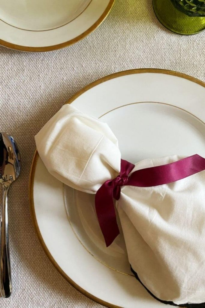 Cloth napkin tied with a wine colored ribbon atop a gold rimmed plate