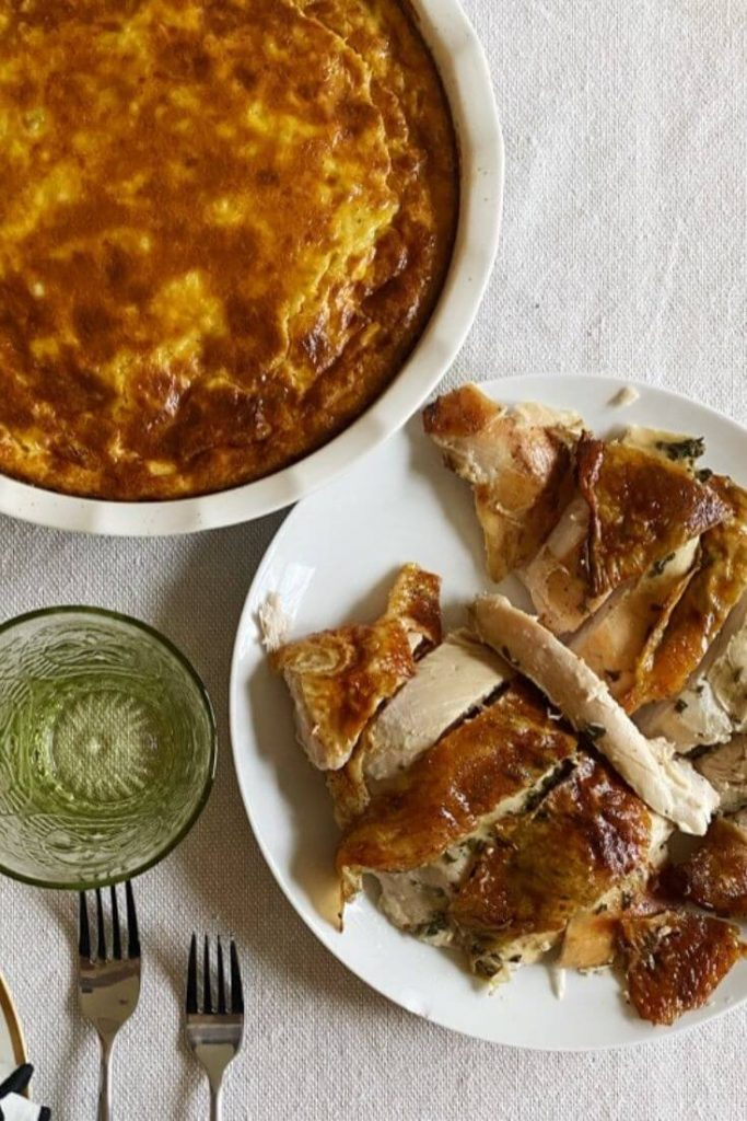 Corn souffle and roasted sliced turkey on a table ready for Thanksgiving