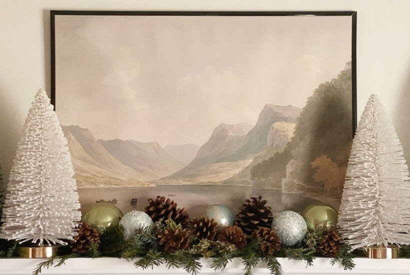 Bottle brush trees flank a landscape print on a shelf with greenery pinecones and ornaments