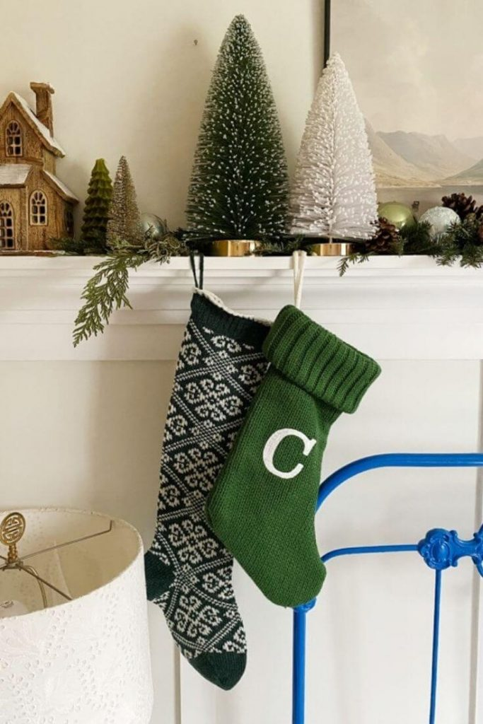 An alternative way to hang stockings for Christmas in your home if you don't have a fireplace mantle. These stockings hang from a decorated mantle shelf for Christmas.