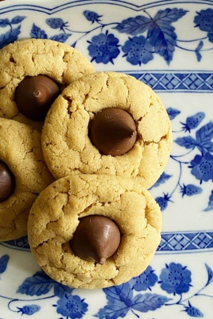 Close up of peanut butter blossom or kiss cookies on a blue and white dish