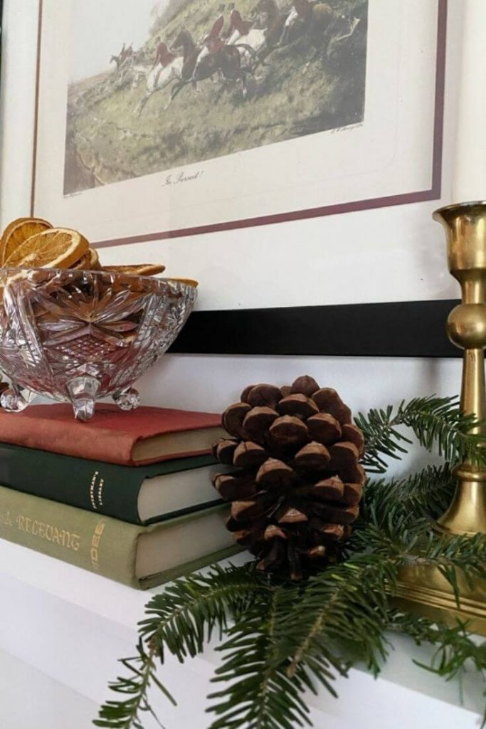 Dried oranges displayed in a glass dish atop a stack of books on a shelf with greenery and pinecones