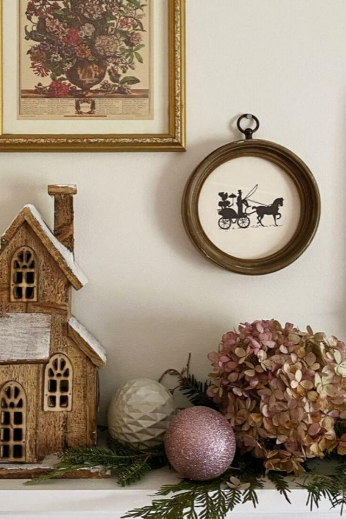 Christmas shelf display with a wooden house bulbs and dried hydrangeas