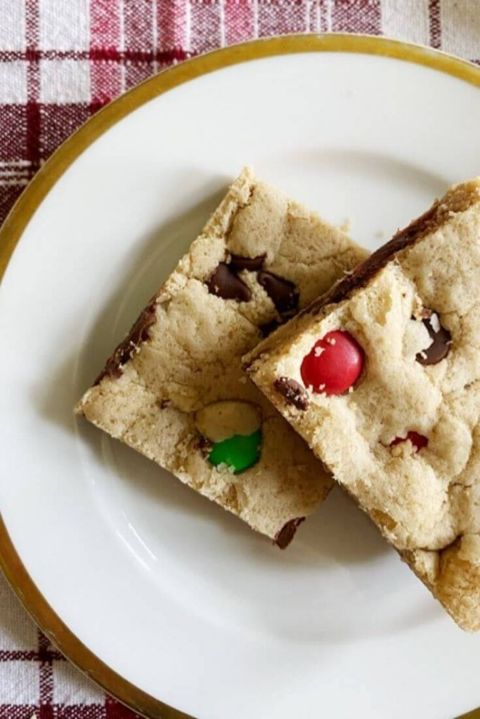 M&M cookie bars on a white plate with golden rim