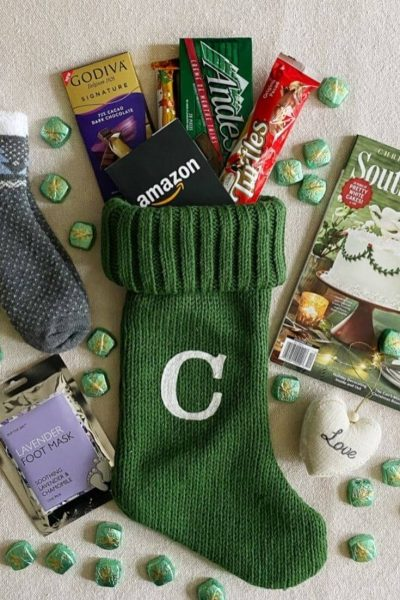 A Christmas stocking and an assortment of stocking stuffer ideas laid out on top of a tablecloth