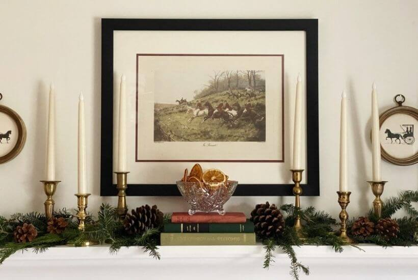 Hunting print hung above a shelf with a traditional Christmas display of greenery pinecones and candlestick
