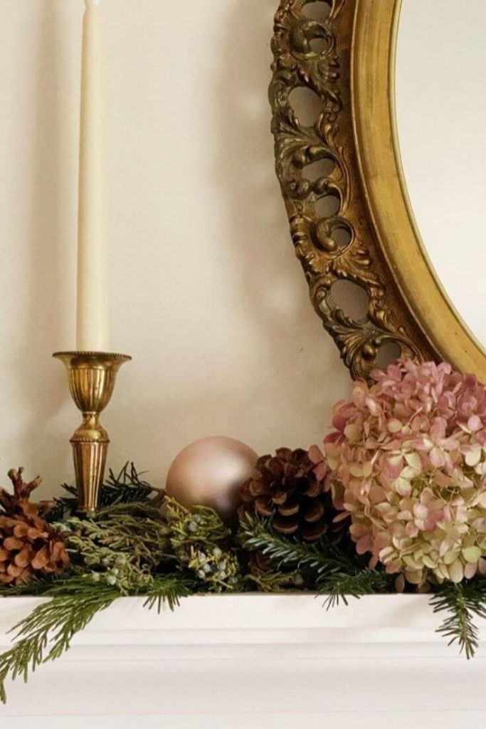 Dried hydrangea greenery pinecones and brass candlestick displayed on shelf